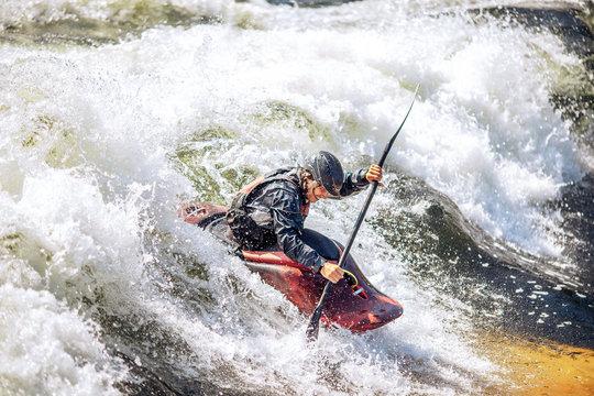 Guy in kayak sails mountain river. Whitewater kayaking, extreme sport rafting