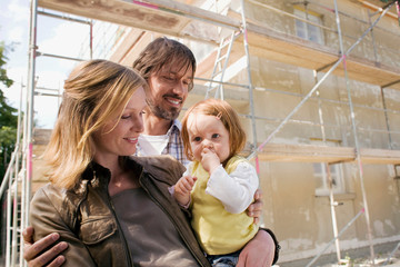 Young family in front of New Home Under Construction