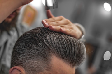 Fotorolgordijn Kapsalon Barber does hair styling. Men's Hair Care.