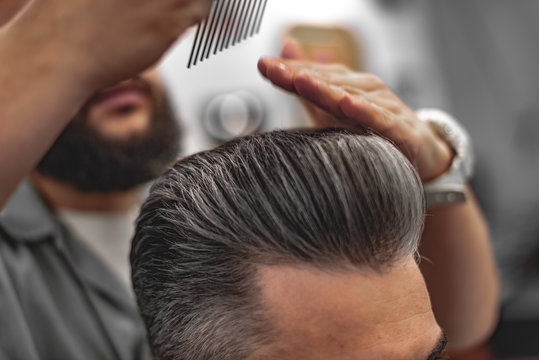 Men's beauty salon. The man makes a haircut.