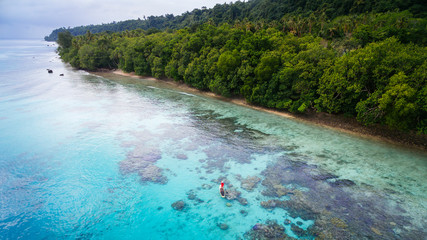 A woman paddling a stand up paddleboard over a coral  reef off the coast of Espiritu Santo, Vanuatu.