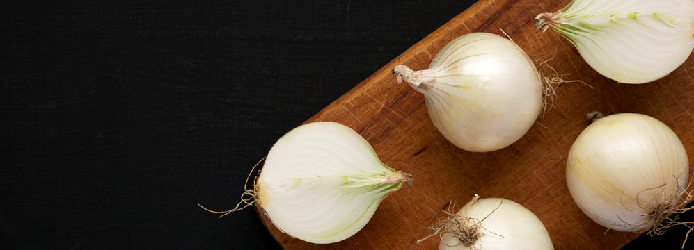 Raw white onions on a rustic board on a black background, overhead view. Flat lay, top view, from above. Space for text.