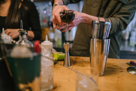 Young barman prepares an alcoholic cocktail in the bar