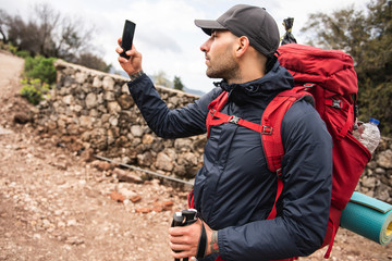 Male hiker taking photo with mobile phone while walking by rural road