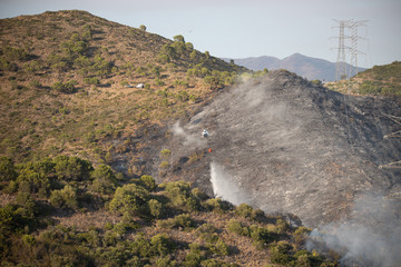 Helicopters putting out a forest fire in the Sierra Bermeja mountains in Estepona, Spain