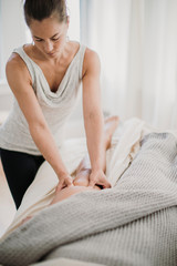 A female massage therapist treats the quadricep of one of her clients