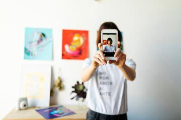 Short hair Artist taking a selfie  at her home art studio