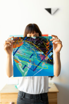Artist showing her art work to the camera