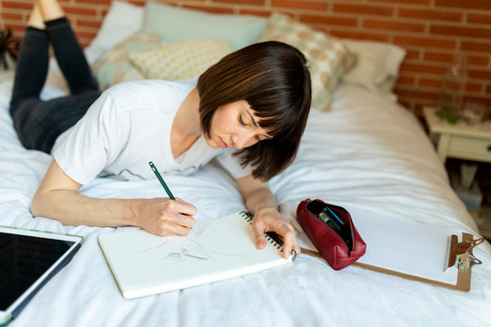Brunette short hair woman drawing in notebook while lying on sof
