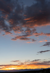 Orange Tinted Dark Clouds with Pale Blue Sky and Distant Mountains at Sunset