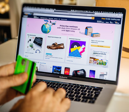 PARIS, FRANCE - JUL 16 2019: Man POV looking at Amazon Australia Prime Day shopping deals on MacBook Pro laptop with Safari Internet browser continuing to offer special deals