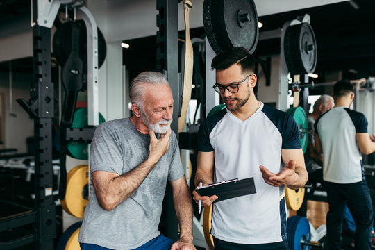 Senior man exercising in gym with his personal trainer.