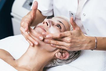 Beautiful senior woman having chemical peeling beauty treatment. The expert beautician is applying...