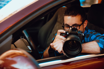 Young paparazzi works from his car.