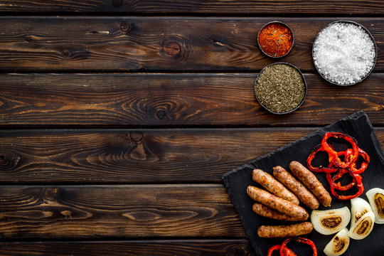 barbecue, sausages, vegetables and kitchen tools on wooden background top view mock up