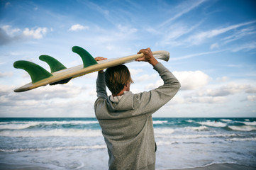 Surfer in gray hoodie carrying his surfboard on his head on the shore of a windy tropical beach