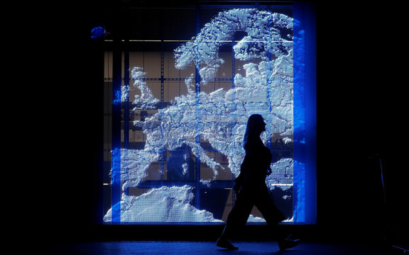 A woman walks past a projection of a map of Europe at the Representation of the European Commission in Berlin