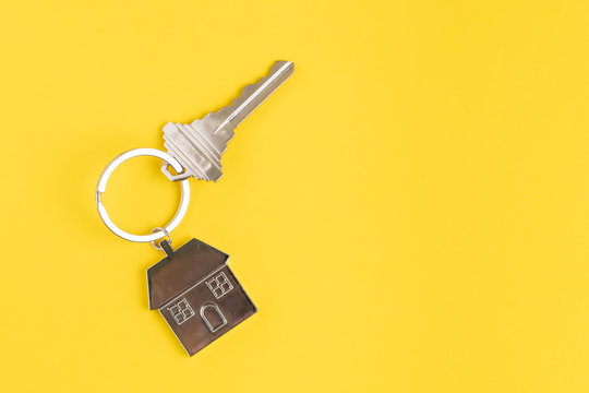 Home key with house keyring or keychain on solid yellow background using as home ownership, mortgage or buy and sell property and real estate