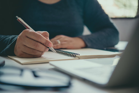 The hand of a man holding a pen and taking notes in a notebook.