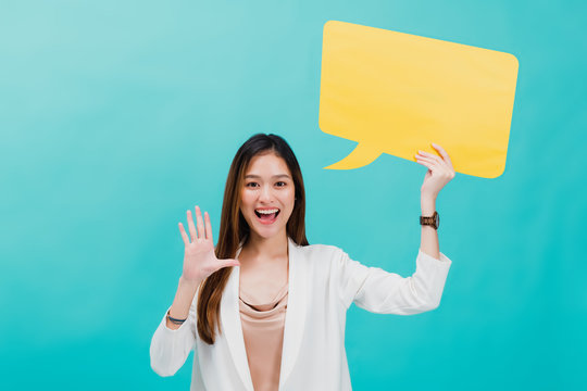 Portrait of confident beautiful asian business woman standing and holding blank yellow bubble speech for text on blue color background.Concept of maketing communication sign idea.