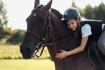 Girl teenager jockey sits on a brown horse, hugs and strokes her.