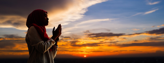 Silhoueitte of young muslim woman pray with beautiful sunset/ sunrise in background