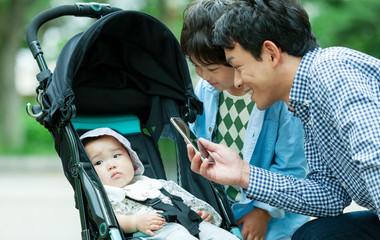 ベビーカーに乗る赤ちゃんの様子を撮影する父親