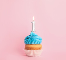 Birthday cupcake with number one candle on pink background