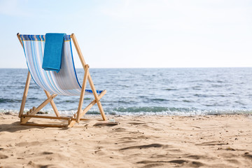 Lounger and towel on sand near sea, space for text. Beach objects