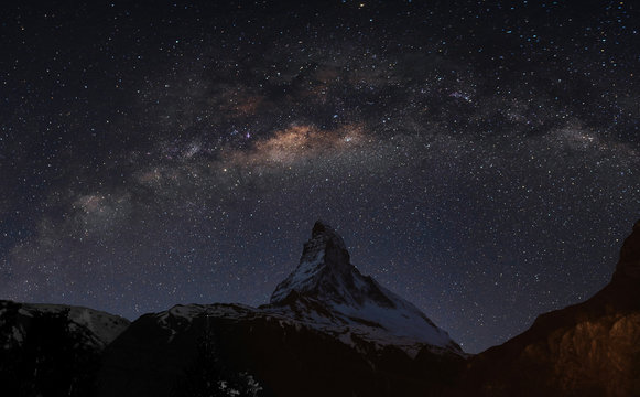 Panoramic Matterhorn mountain at night in Switzerland with starry sky and milky way