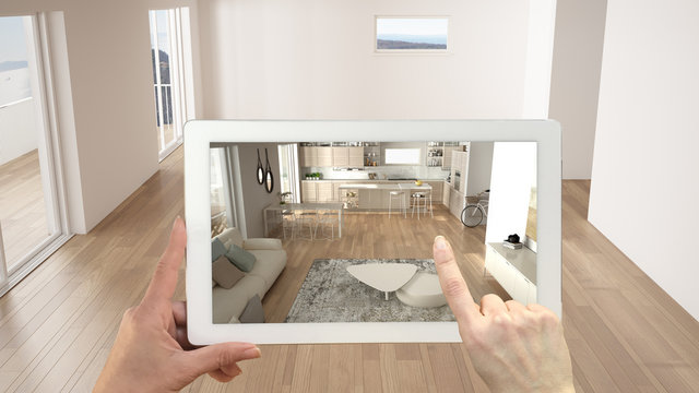 Augmented reality concept. Hand holding tablet with AR application used to simulate furniture and design products in empty interior with ceramic floor, modern white kitchen