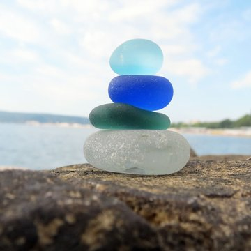Colorful sea glass pyramid on beach rock with seascape background. Seaglass stack beach combing