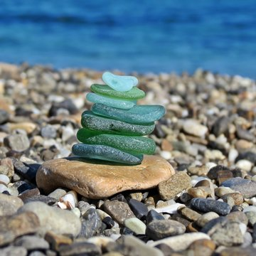 Green shades seaglass stack on rock seashore with seascape background. Sea glass pyramid beach combing