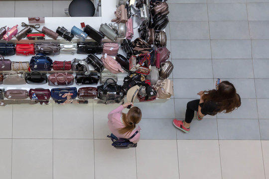 Two young girls (women) stand at the counter with leather bags in the Mall and examine them.