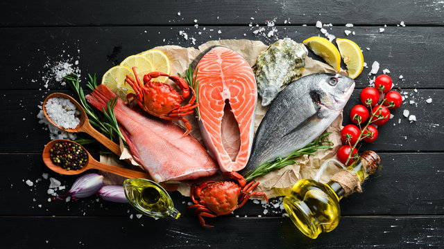 Seafood on a black wooden background. Banner Top view. Free space for your text.