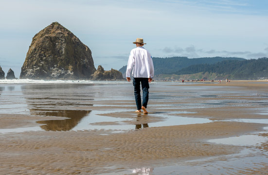 A man in an embroidered shirt and hat walks along the shore of the Northwest Pacific