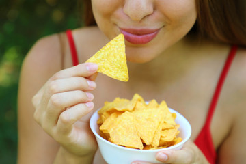 Close up portrait of woman eating tortilla chips with a full bowl in her hand.