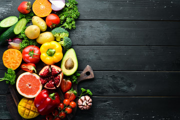 Foto op Plexiglas Keuken Fresh fruits, vegetables and berries. On a black background. Banner Top view. Free space for your text.