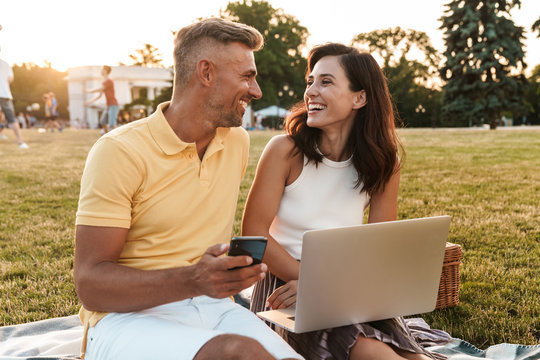 Portrait of joyous middle-aged couple holding cellphone while using laptop computer during picnic in summer park