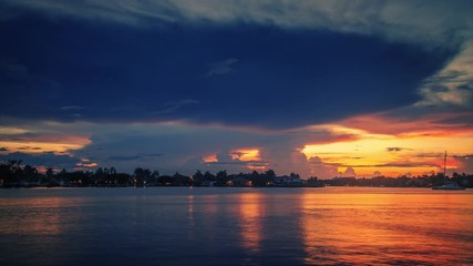 Fotobehang - Epic storm clouds in colorful sunset sky over water reflections in Miami, Florida. Timelapse, 4K UHD.