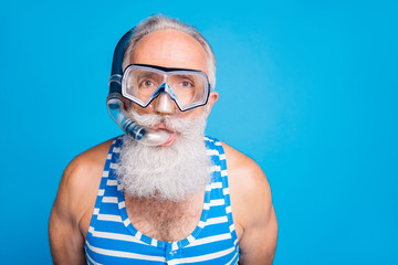 Close up photo of funky retired man having snorkel gear look wearing striped swim wear isolated over blue background