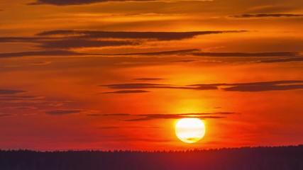 Fotobehang - Sunset sun setting behind distant forest skyline. Timelapse, 4K UHD.