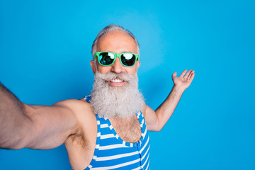 Close up photo of retired man in eyeglasses eyewear holding his palm making selfie wearing striped swim wear isolated over blue background