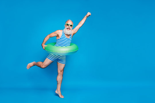 Full length photo of excited retired pensioner with grey hair raising his fist holding toy circle wearing striped swimwear glassses isolated over blue background