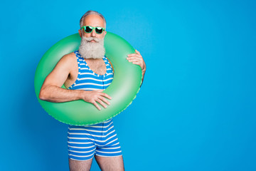Portrait of attractive man with rubber circle looking in eyewear eyeglasses wearing striped costume isolated over blue background