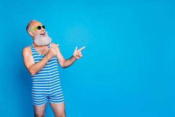 Portrait of his he nice attractive confident cheerful cheery glad gray-haired man pointing ad advert sale discount black Friday copy space isolated on bright vivid shine blue background