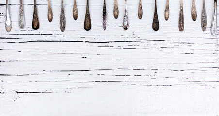 Vintage cutlery - spoons, forks and knives on an old wooden background. Fototapete