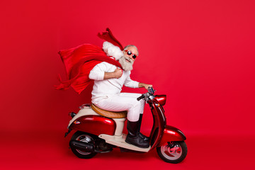 Full length profile side photo of funny pensioner carrying bag with gifts sitting on motorcycle hurrying wearing white sweater pants boots isolated over red background Fototapete