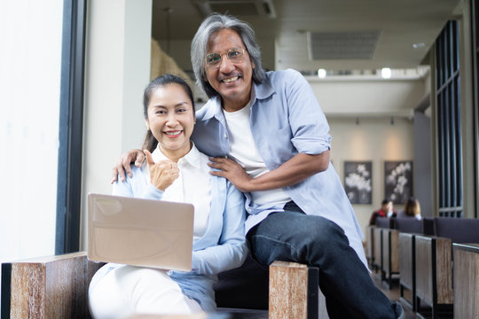 Asian of loving senior couple using laptop computer in cafe,Family concept