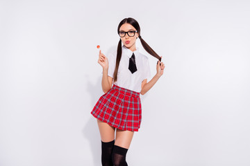 Portrait of her she nice-looking attractive lovely glamorous cheerful cheery alluring enticing girl wearing checked skirt licking lolly pop isolated on gray light white background